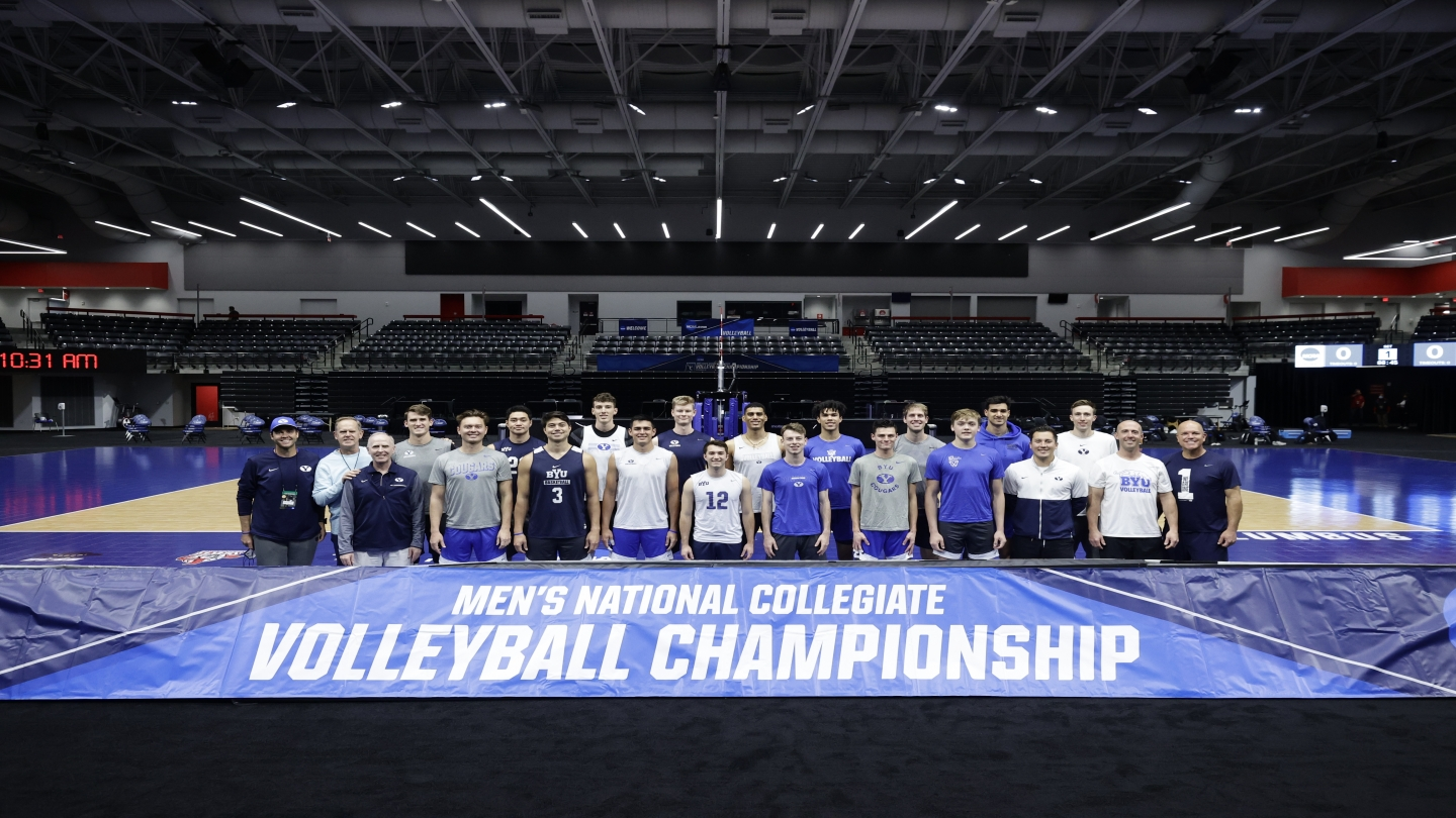 mens volleyball team standing behind national championship sign